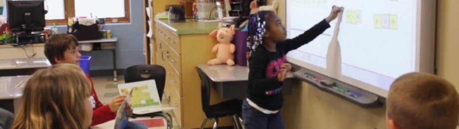 Young girl using smart board at school